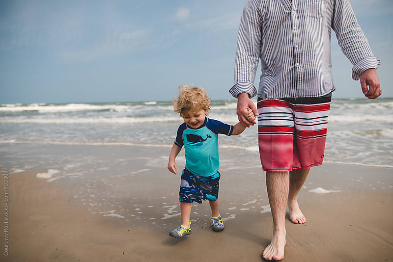 Dad and son walk on beach by Courtney Rust for Stocksy United
