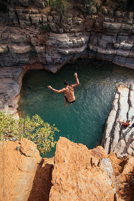 Young man jumping from a cliff to the water by Alejandro Moreno de Carlos for Stocksy United