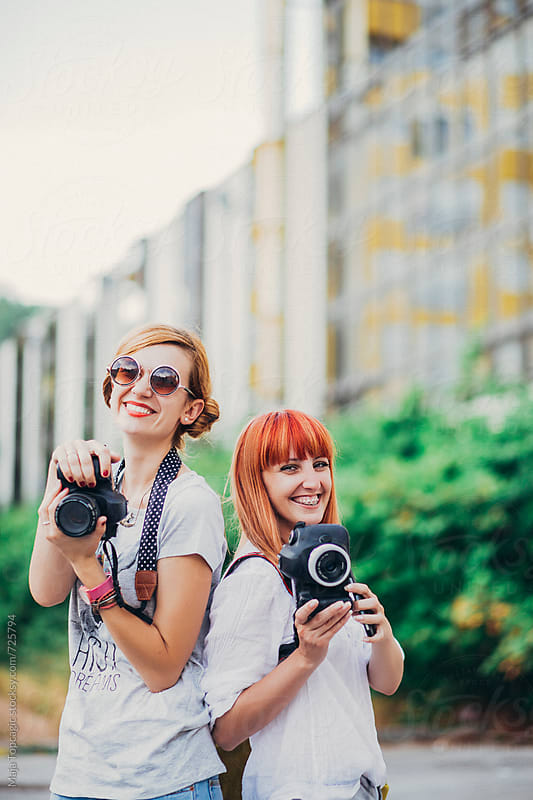Two young female photographers smiling by Maja Topcagic for Stocksy United