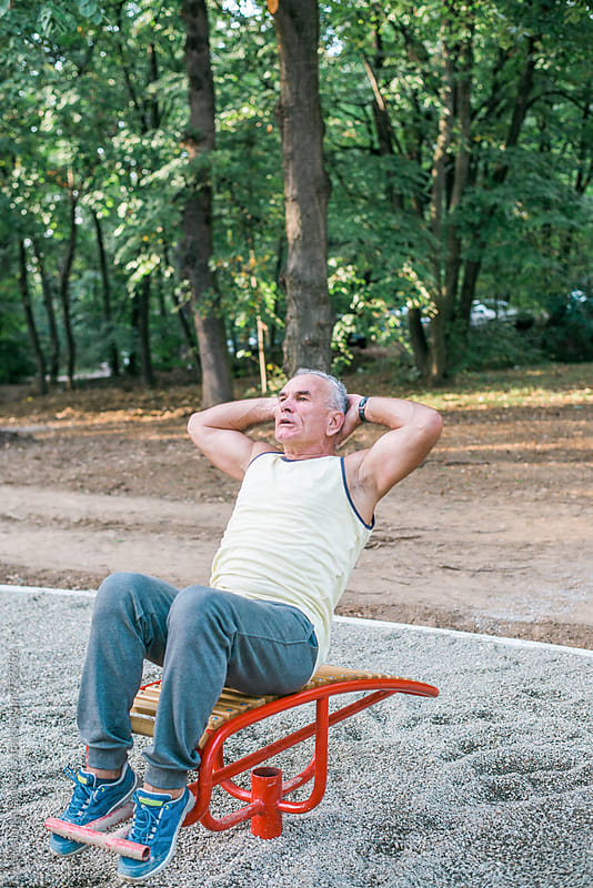 Gray-haired Man Doing Crunches in the Park by Aleksandra Jankovic for Stocksy United