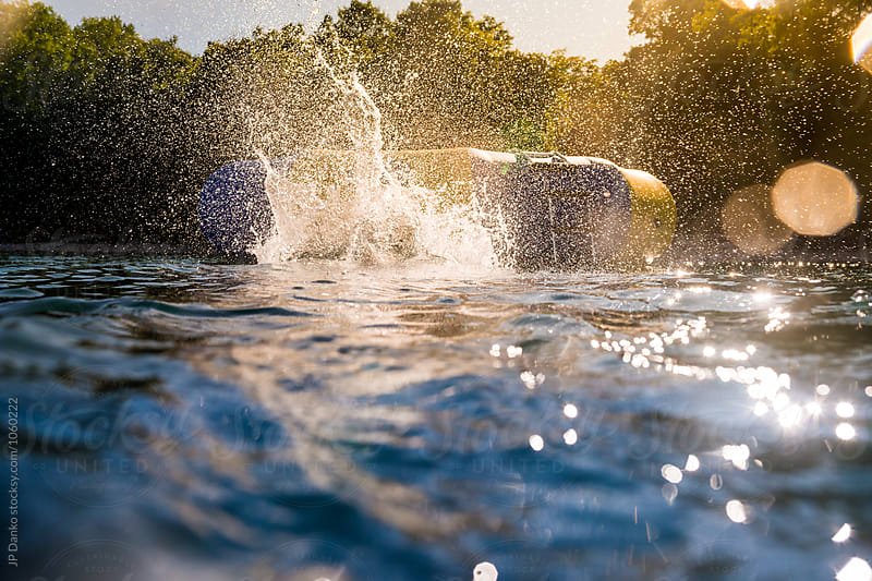 Splash from Boy Jumping Into Summer Lake From Water Trampoline At Cottage at Sunset by JP Danko for Stocksy United