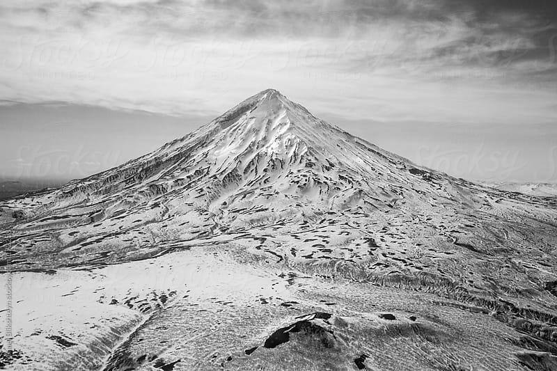 Black and white aerial view of a snow-covered extinct volcano by Mihael Blikshteyn for Stocksy United