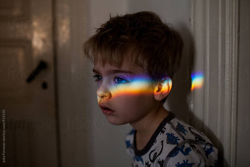 Boy looking forward with rainbow of light across his face. by Julia Forsman for Stocksy United
