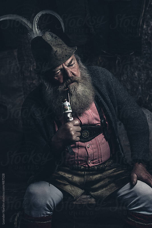 thoughtful old full bearded man sitting indoors on a bench smoking a pipe by Leander Nardin for Stocksy United