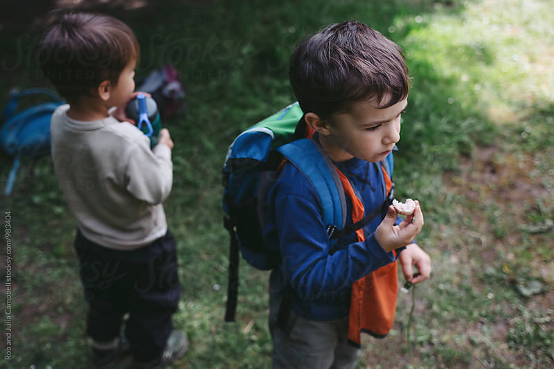 Young caucasian boys eating at nature preschool by Rob and Julia Campbell for Stocksy United