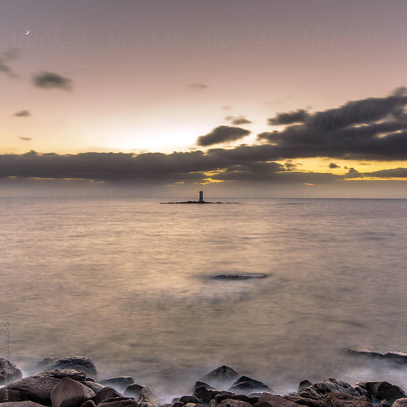 Lighthouse at sunset, long exposure by Luca Pierro for Stocksy United