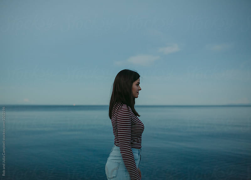 Portrait of young caucasian girl standing near water on beach by Rob and Julia Campbell for Stocksy United