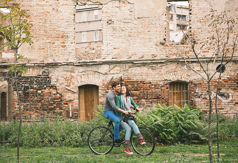 Smiling Couple on a Bike by Lumina for Stocksy United
