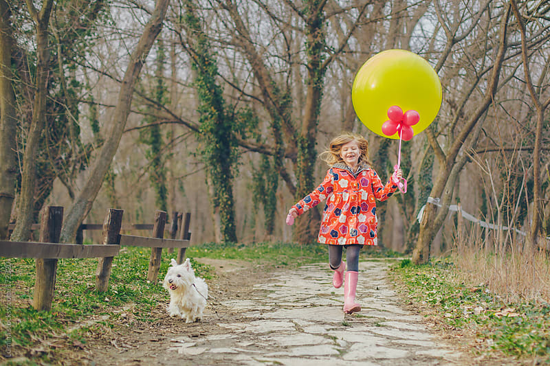 Happy Girl Walking Her Dog by Lumina for Stocksy United