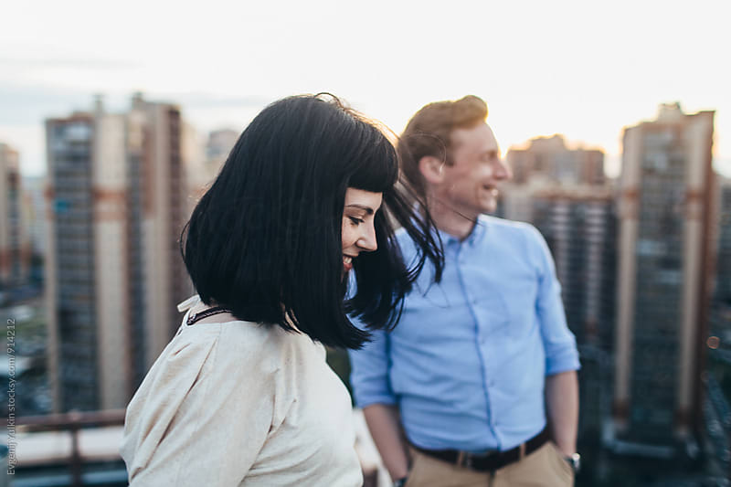 Young couple smiling standing on the rooftop by Evgenij Yulkin for Stocksy United