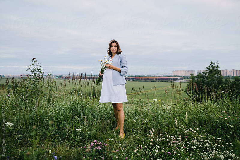 Pregnant female with camomile bouquet  by Evgenij Yulkin for Stocksy United