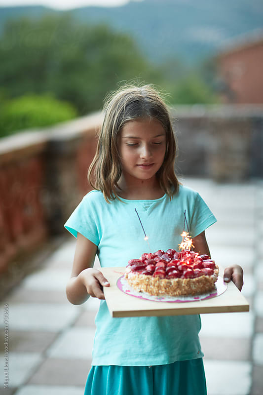 Little girl holding a birthday cake of strawberries by Miquel Llonch for Stocksy United