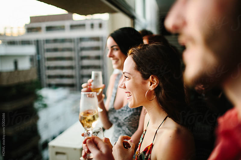 A group of friends look out the window while sipping on champagne  by HOWL for Stocksy United