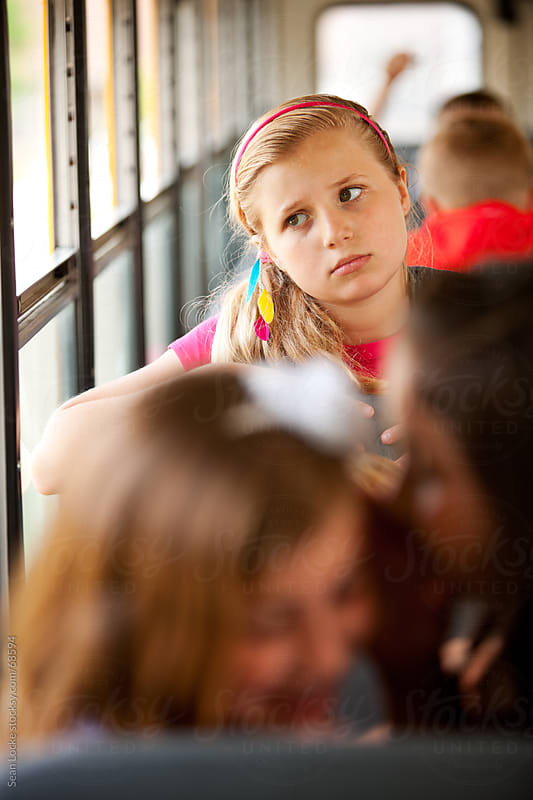 School Bus: Girl Upset Others are Gossiping by Sean Locke for Stocksy United