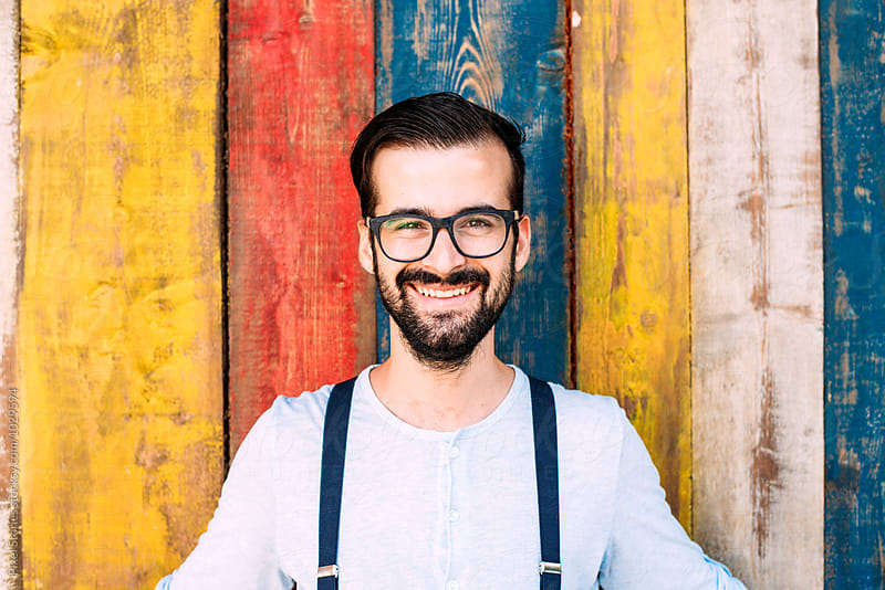 Young man smiling against colorful wall by Pixel Stories for Stocksy United