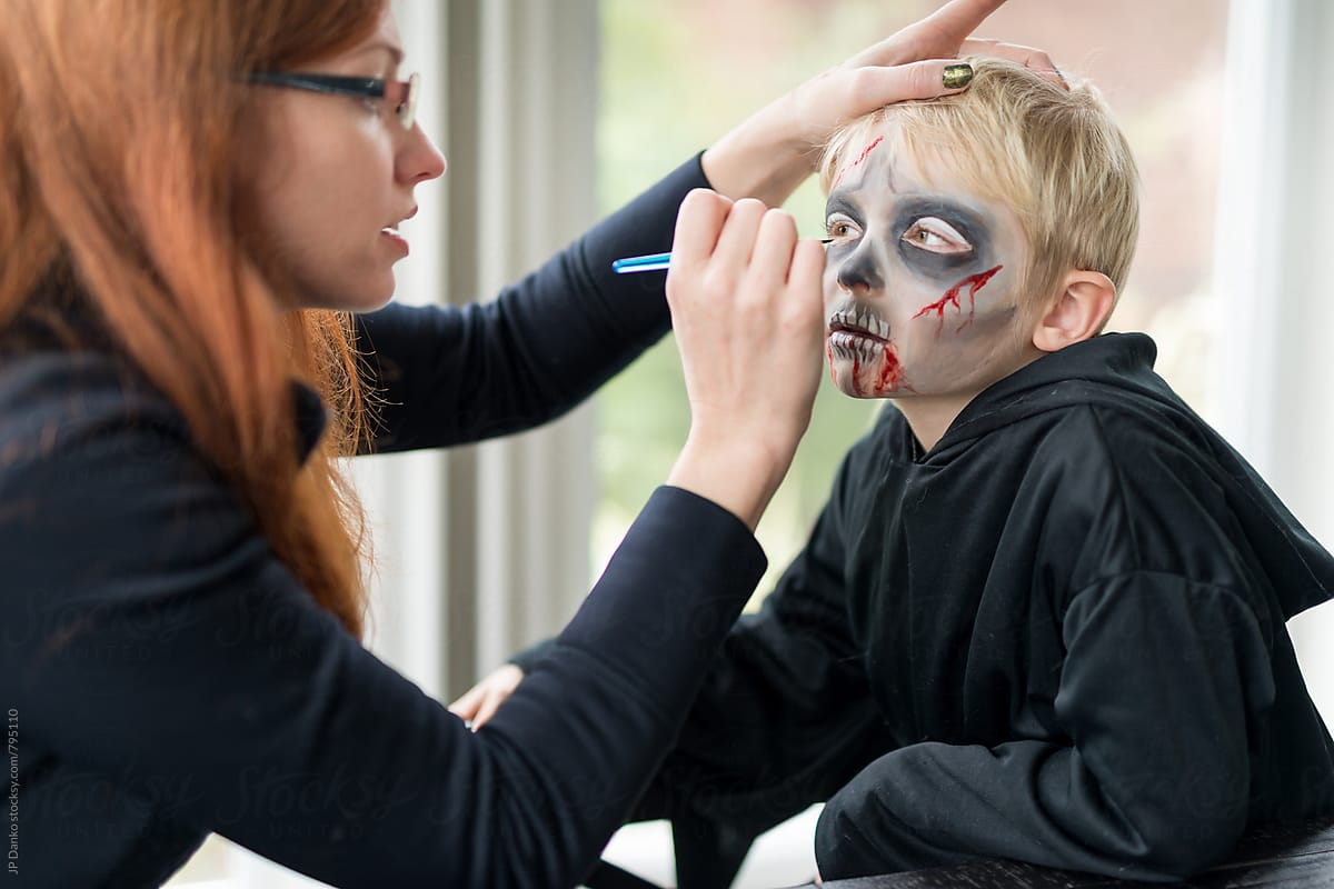 mother applying scary halloween costume make up for boy | stocksy united