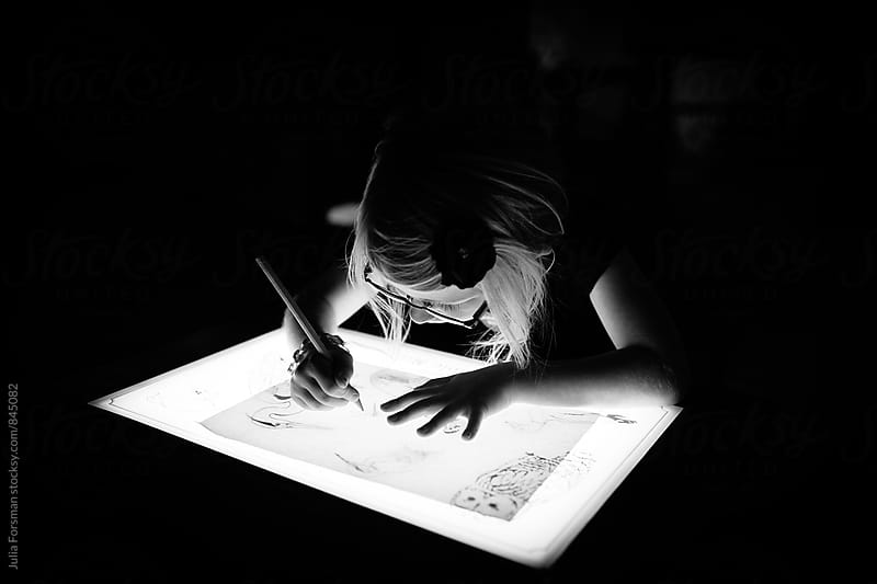 Black and white of girl using a light-box to trace a picture. by Julia Forsman for Stocksy United
