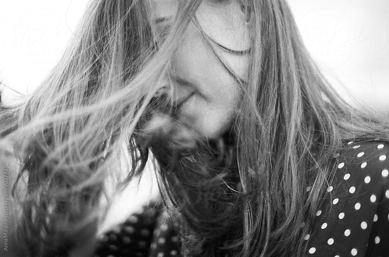 A black and white film portrait of young beautiful woman with a wind blowing her hair by Anna Malgina for Stocksy United