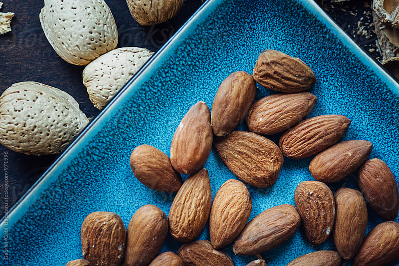 Almonds closeup on a blue plate by Gabriel (Gabi) Bucataru for Stocksy United