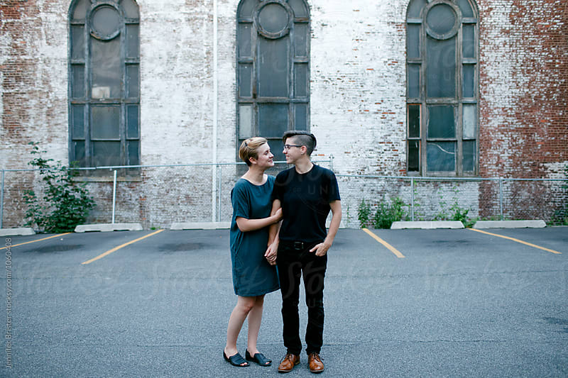 An adorable couple standing close to each other in parking lot by Jennifer Brister for Stocksy United
