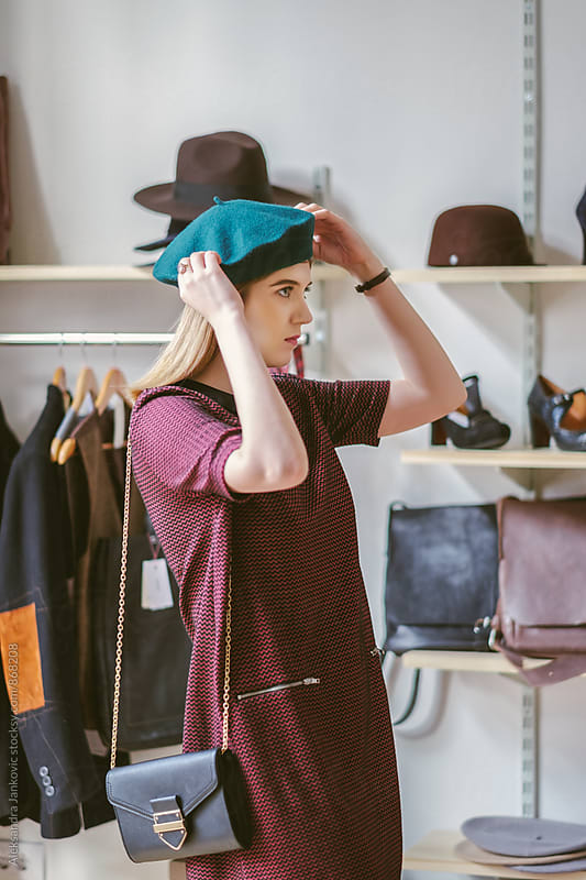 Beautiful Woman Trying Out a Beret in the Clothing Store by Aleksandra Jankovic for Stocksy United