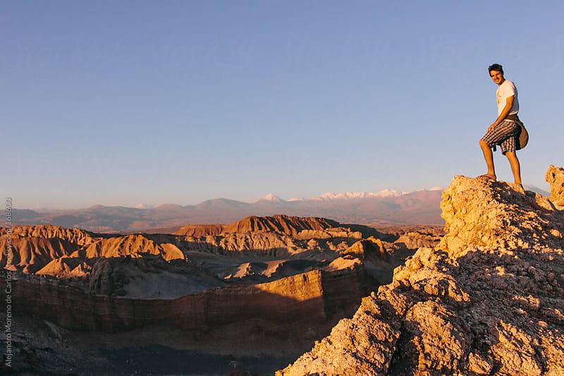 Man on edge of cliff on desert landscape in Atacama desert, Chile by Alejandro Moreno de Carlos for Stocksy United