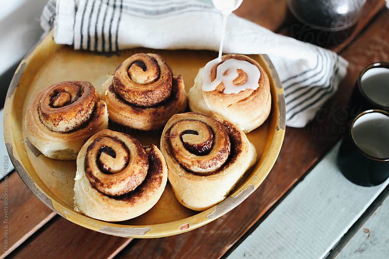 pouring icing on cinnamon buns on wooden table by Treasures & Travels for Stocksy United