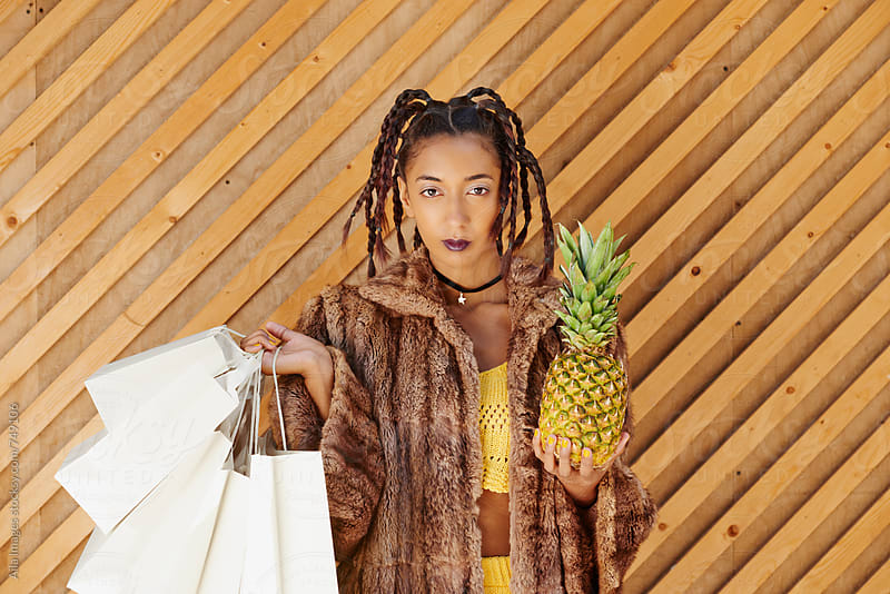 Nineties Yellow Girl shopping with Pineapple by Aila Images for Stocksy United