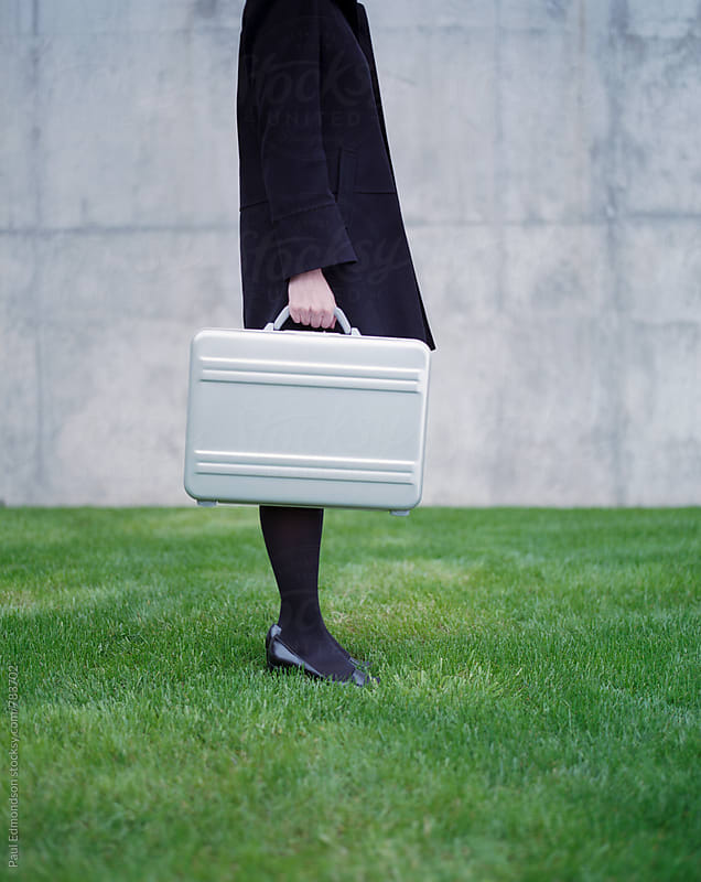 Woman standing on lush green grass, holding metal briefcase by Paul Edmondson for Stocksy United
