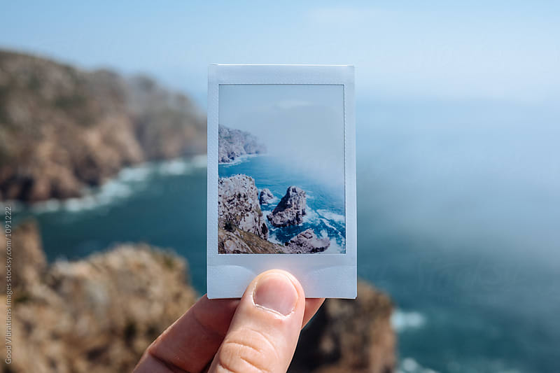 Hand holding polaroid of coastline by Good Vibrations Images for Stocksy United