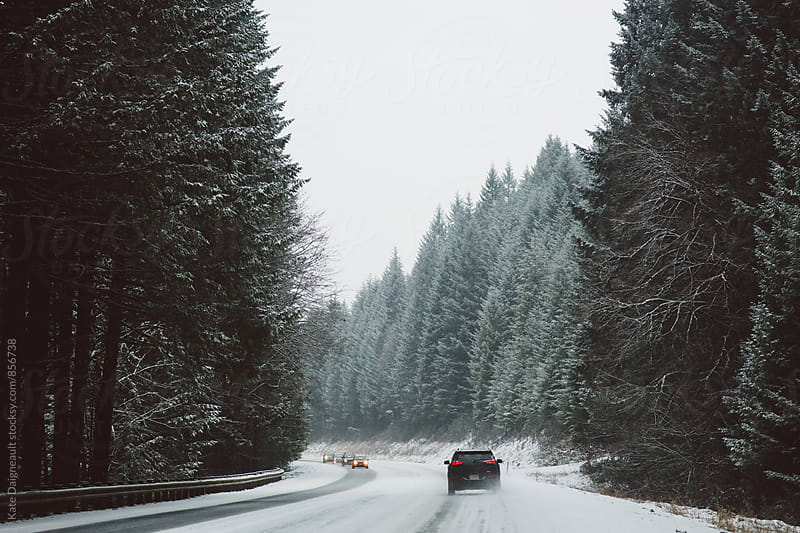 Drive through a snowy mountain pass.  by Kate Daigneault for Stocksy United