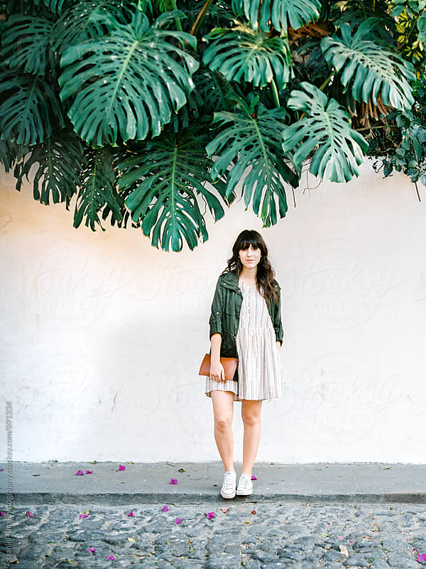 Woman standing under large leaves by Daniel Kim Photography for Stocksy United