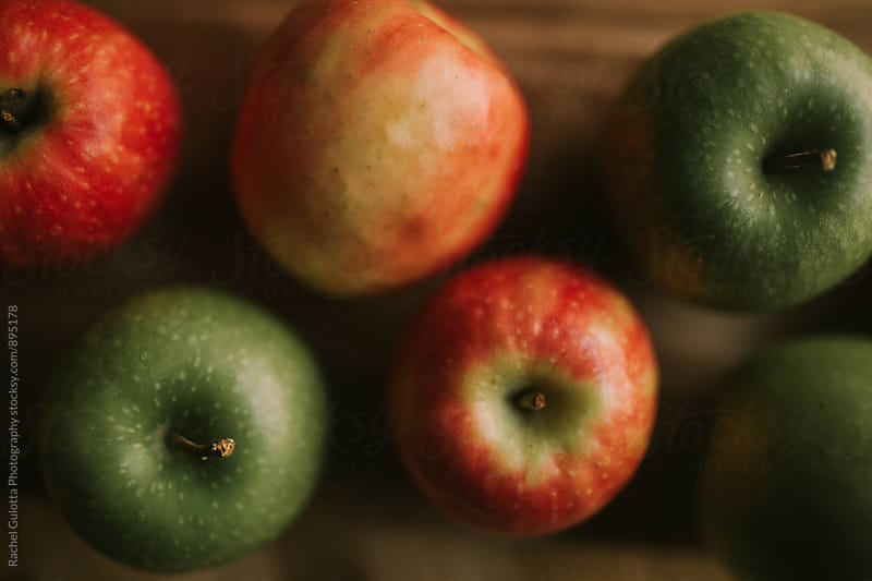 Green and Red Apples Laying on a Table by Rachel Gulotta Photography for Stocksy United