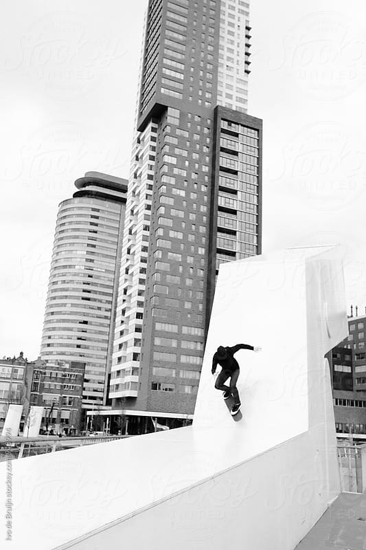 Skater doing a trick in the city. Photo shot in black and white. Photo in black and white. by Ivo de Bruijn for Stocksy United
