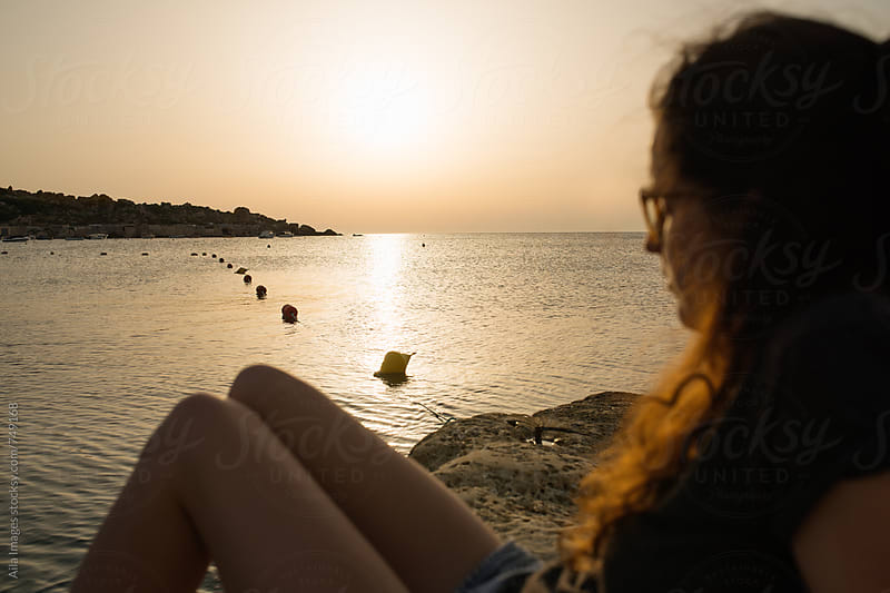 Woman watching sunset over ocean on vacation by Aila Images for Stocksy United
