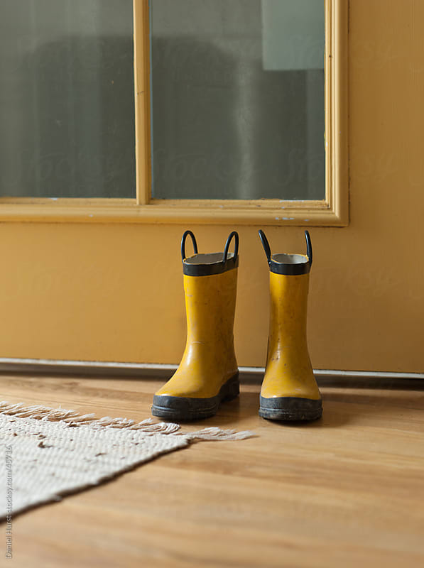 Pair of boots by door by Daniel Hurst for Stocksy United