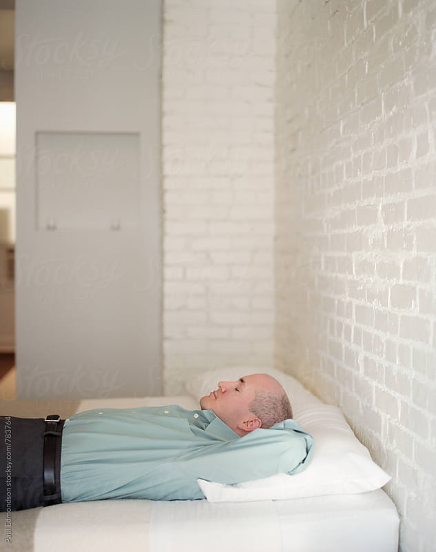 Businessman resting on bed in modern, sparse hotel room by Paul Edmondson for Stocksy United