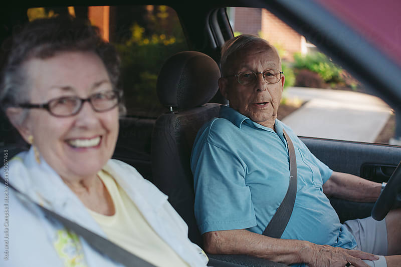 Caucasian senior couple driving in minivan together by Rob and Julia Campbell for Stocksy United