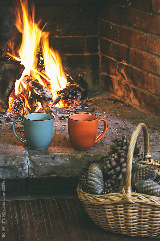 Fireplace in a comfortable home. Basket of pine cones and two hot cups. by BONNINSTUDIO for Stocksy United