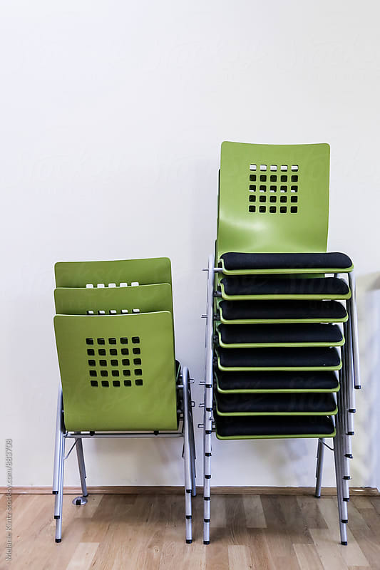 Green chairs stacked by Melanie Kintz for Stocksy United