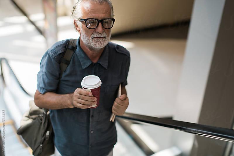 Senior Businessman on an Escalator by Mosuno for Stocksy United