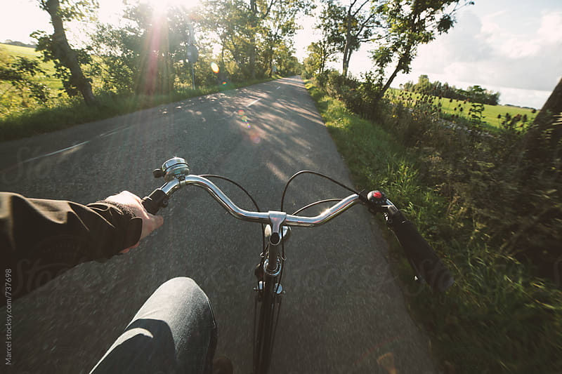 Cycling man in morning sun on rural road by Marcel for Stocksy United