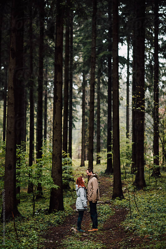 Couple standing in the middle of the forest by Boris Jovanovic for Stocksy United