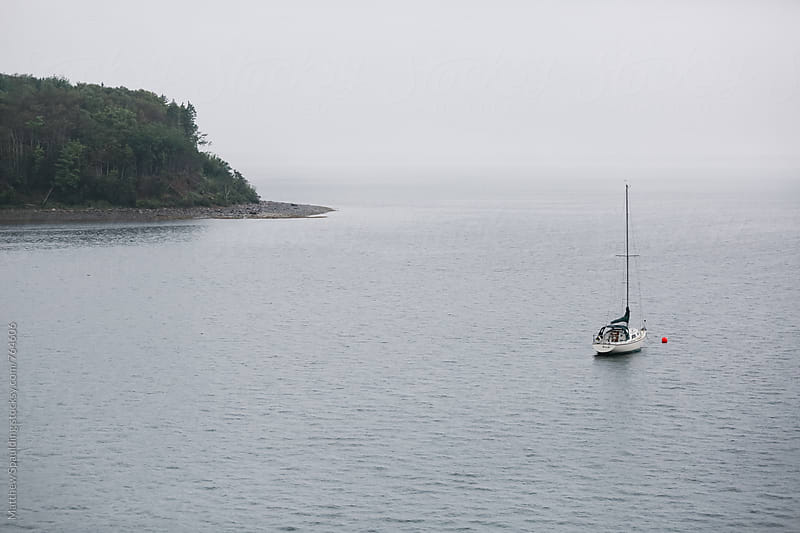 Sailboat on mooring protected in cove harbor by Matthew Spaulding for Stocksy United