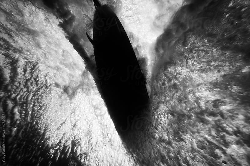An underwater view of a surfboard slicing through the water by Gary Parker for Stocksy United