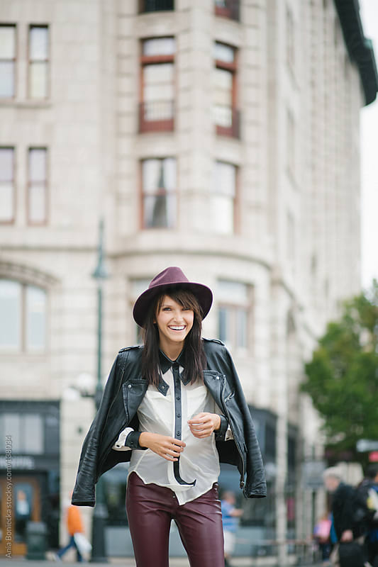 A stylish brunette laughing on the street while adjusting her top by Ania Boniecka for Stocksy United