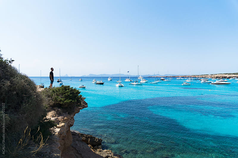 Young man looking at paradise cove in Mediterranean Sea by ACALU Studio for Stocksy United