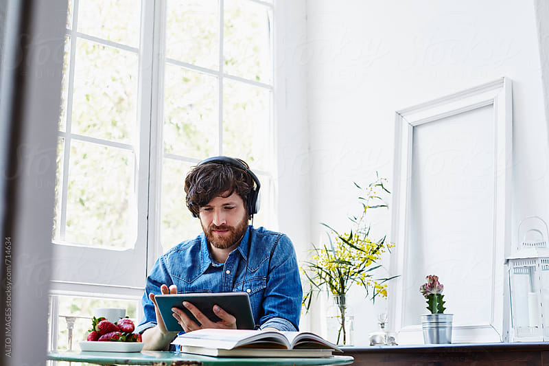 Man Listening Music On Digital Tablet At Home by ALTO IMAGES for Stocksy United