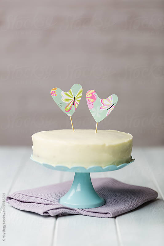 White frosted round carrot cake on blue stand by Kirsty Begg for Stocksy United