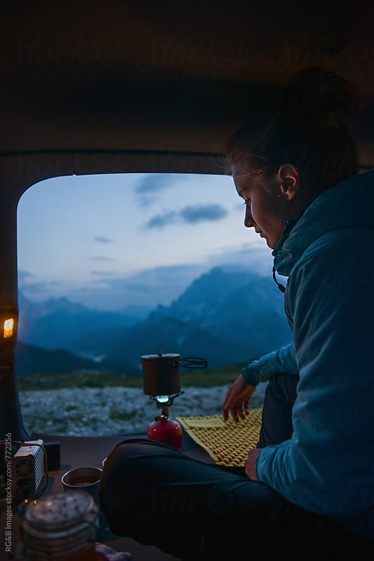 Woman cooking inside the car at dusk by RG&B Images for Stocksy United